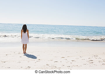 Brunette in white sun dress walking to the sea on the beach