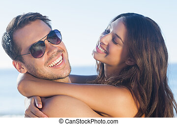 Cheerful loving couple hugging each other on the beach