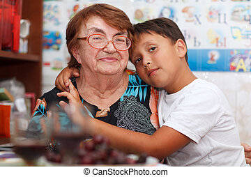 Grandson and grandmother - Grandson is hugging his...