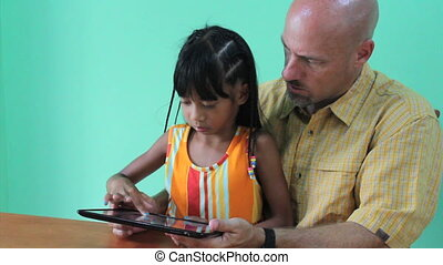 Father and Daughter Playing On Tablet - A father plays games...
