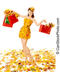 Autumn woman with shopping bags in dress of maple leaves