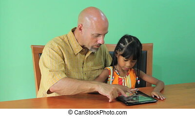 Asian Girl Learns How To Use Tablet - A cute little 7 year...