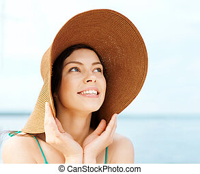Girl in hat standing on the beach - summer holidays and...