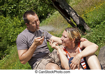 Couple with e-cigarettes outdoor - a Couple with...