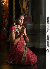 Indian woman praying - Young Indian woman in traditional...