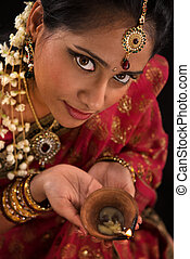 Diwali Indian female with oil lamp - Close up portrait of...