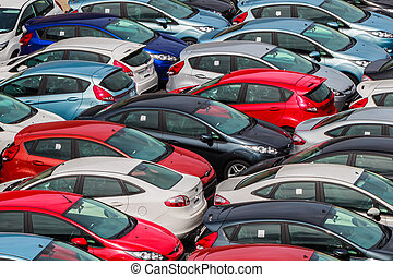 Brand new motor vehicles crowed in a parking lot waiting for...