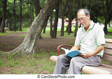 happy senior man sitting on bench and reading book