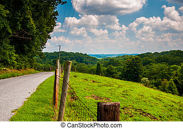 Fence and rural backroad atop a hill in Baltimore County,...