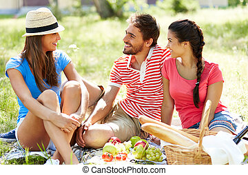 Weekend picnic - Happy young friends having picnic in the...