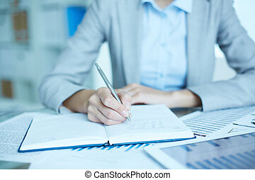 Writing business plan - Image of businesswoman writing in...