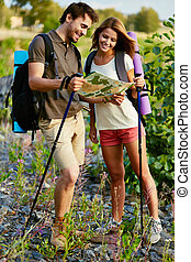 Trippers - Portrait of young hikers looking at map in the...