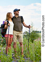 Hikers with backpacks - Couple of smiling trippers standing...