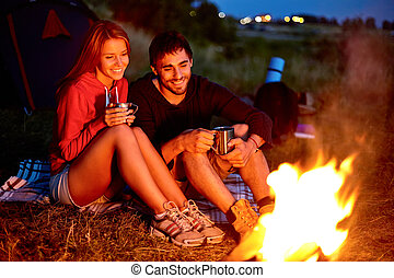 Campers by the fire - Young couple sitting on the ground and...