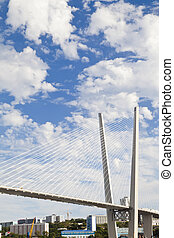 Big suspension bridge against the blue sky in beams of a...