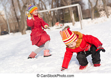 Children in Winter Park playing snowballs, actively spending...