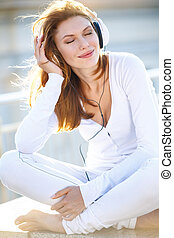 Joyous young woman listens to music