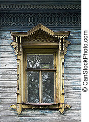 Old wooden window with carved platbands, Tutaev, Russia