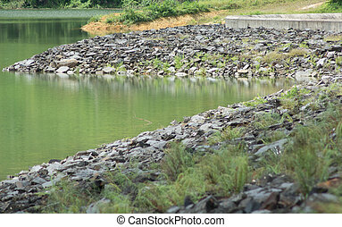 Stone bank of the river in reservoir