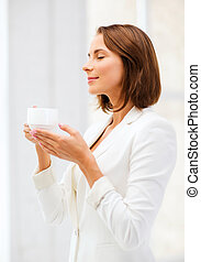 Businesswoman with cup of coffee in office