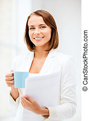 Woman with cup of coffee and folders - business concept -...