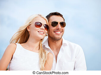 Couple in shades at sea side - summer holidays and dating...