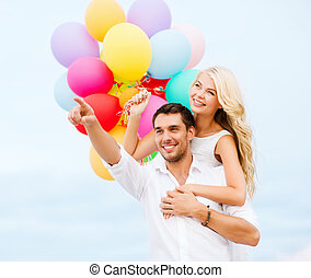 Couple with colorful balloons at sea side - summer holidays,...