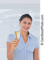 Attractive businesswoman holding champagne