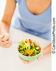 Woman eating salad with vegetables - healthy food and...