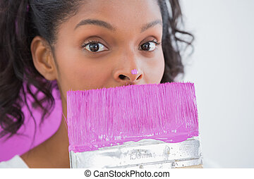 Pretty woman holding paintbrush with pink paint on her nose...