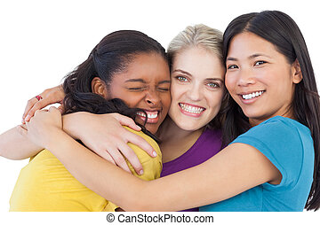 Diverse young women hugging each other on white background