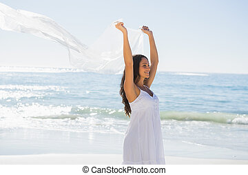 Happy brunette in white sun dress holding sarong on the...