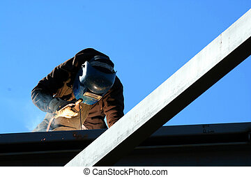 Welder - A welder on the roof of a construction site