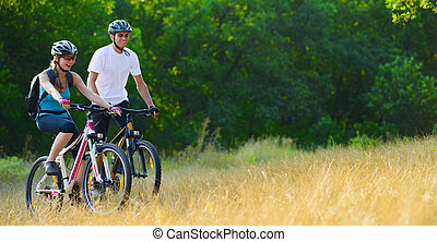 Young Happy Couple Riding Mountain Bikes Outdoor. Healthy...