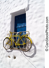 Decorative bicycle hanging from a window in a Greek house on...