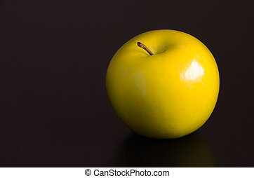 Golden apple. - Golden apple on a wooden table.