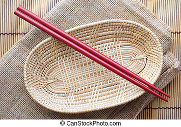 Two chopsticks next to a red and white basket