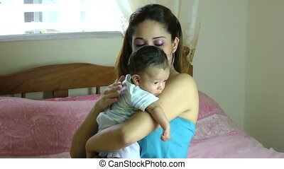 Hispanic Latina mother holding drooling baby over shoulder...