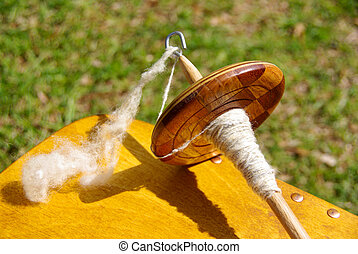 drop spindle - a drop spindle used to spin wool into yarn