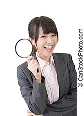 Young asian businesswoman holding magnifying glass -...