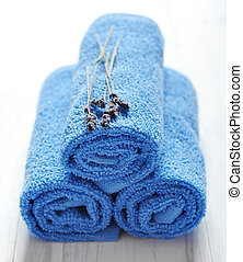 Blue spa towels pile with lavender on white wooden...