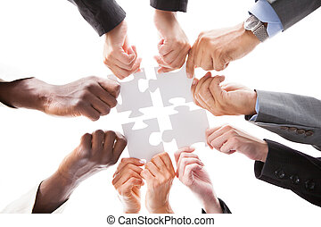 Businesspeople Holding Jigsaw Puzzle - Close-up Photo Of...