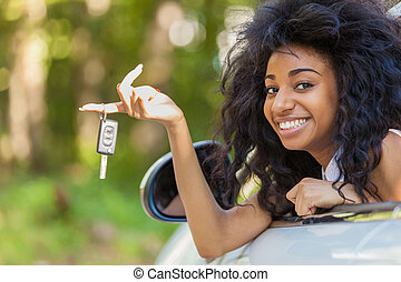 Young black teenage driver holding car keys driving her new...
