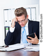 Contemplated Businessman Holding Calculator