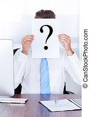 Businessman Holding Question Mark Sign On Paper In Front Of...