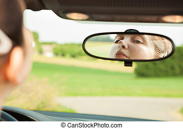 Woman Looking At Mirror In Car - Young Woman Looking At...