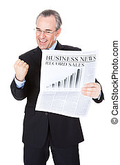 Businessman With Newspaper - Mature Businessman Reading...