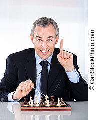 Mature businessman playing chess and gesturing indoors