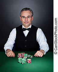 Portrait of a croupier with gambling chips on table