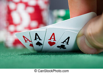 Poker player holding playing cards - Close-up of a poker...